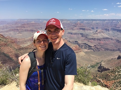 Husband with his arm around AMI employee Sara Szwaja, both dressed in hiking gear and smiling in front of the Grand Canyon on a clear day